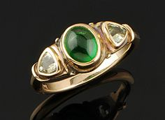 3 stone ring oval Tsavorite Garnet cabochon & a pair of 4.5mm faceted trillion green Sapphires, in 14K yellow gold with 18K yellow gold bezels.