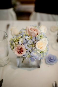Small wedding centerpieces. Blue hydrangea and pale pink roses