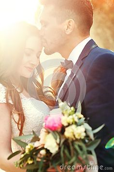 Couple hugging at sunset, lovers couple kissing in sunset. Wedding ceremony outdoors. Beautiful bride and groom with bouquet of flowers. White wedding dress for bride. Love wedding couple hug. Blurred