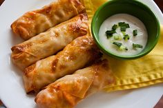 Buffalo Chicken Rolls (makes 12)  12 egg roll wrappers  1 cup cooked and shredded chicken 1/2- 2/3 cup Frank's Red Hot Sauce 1 cup crumbled blue cheese (4 oz) 1 cup broccoli slaw or cole slaw (dry) Blue cheese dressing, for serving