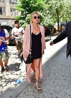 Margot Robbie in a black slip mini dress, blush pink Spell & The Gypsy Collective robe, hobo bag, round sunglasses and gladiator sandals.
