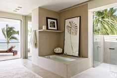 The master bath at the Legorreta + Legorreta–designed Mexico vacation home of Cindy Crawford and Rande Gerber makes the most of its paradisiacal surroundings with an outdoor shower adjacent to the stone tub.