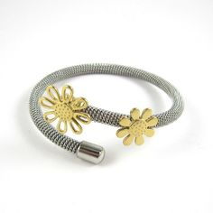 Designer inspired Daisy bangle in sleek durable stainless steel with gold plated daisy detail This bangle will fit most wrist sizes and is flexible
