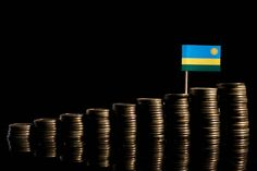 rwanda flag with lot of coins isolated on black background