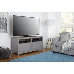 """The Altra Carver TV Stand is perfect for all your entertainment needs. The open shelves provide space for a DVD player, cable box or sound bar. Hide your DVDs, video games and accessories behind the 2 large doors. The stand accommodates most flat panel TVs up to 60"""" wide with a maximum weight of 95 lbs. The Altra Carver TV Stand features a soft gray finish with a distressed woodgrain top that creates a refined, clean look in your home. Altra Carver TV Stand requires assembly upon delivery."""