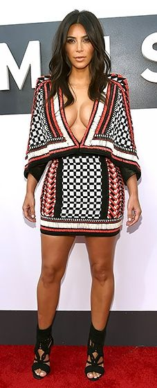 Kim Kardashian flaunted her cleavage in a low-cut mixed print dress at the 2014 VMAs.