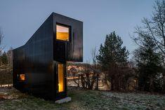 die Hausfassade besteht aus in Schwarz lackierte Holzbrettern