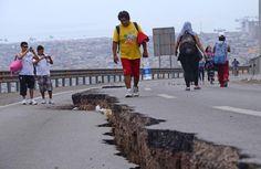 Warga berjalan di sebuah jalan yang rusak akibat gempa di kota Iquique, Chile utara.