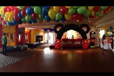 Mickey Mouse Theme Party. Party Room Decor with Balloon Drop. Mickey Mouse balloon arch and bouncy houses.