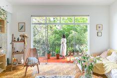 Sala de estar tem tons neutros, móveis em madeira e texturas. Ao fundo varanda na altura da copa das árvores.