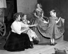"Emmy Gifford and actresses Alison Teal, Ann Kennedy and Mary Campbell in costume for the Omaha Junior League's production of ""Grandmother's Magic Clock"" at the Joslyn Concert Hall. This photo of the performers ran April 18, 1954. Written by Omahan Val Teal, the play for youths delved into the city's history through a family's covered-wagon trip west. THE WORLD-HERALD"