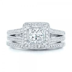 #102809 This elegant engagement ring features a princess cut diamond prong set in white gold, with a diamond halo, as well as bright cut set diamond accents...