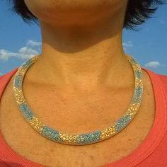 striped nylon mesh necklace  * snow white nylon mesh tubing  * filled with golden and turquoise glass seed beads  * mesh creates a pixelated effect  * silver tone magnetic tube clasp  * about 19 1/2'' long  * tube diameter about 9 mm