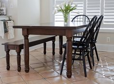 Antique horse country oak dining table with matching horse country oak bench and painted 8-spindle bow-back chair in antique oak.