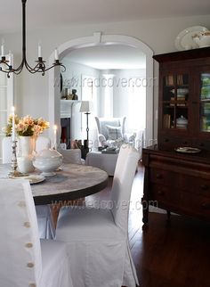 LOVE this combination of cherry hutch, distressed table, beautiful white slipped chairs!