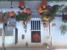 Front porch decorated with pumpkins in every color, hay, orange lights, mums, & scarecrows.