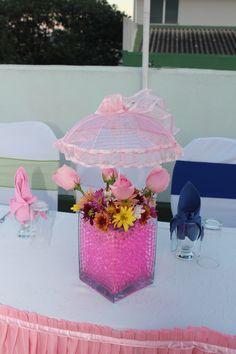 Centro de mesa en base de cristal con sombrilla de tela, rosas y shastas. Candy Candy