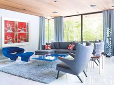 Artful Affair - In the living room, an Yves Klein Table Bleue is flanked by a vintage Pierre Paulin Ribbon chair and a pair of Hans Wegner Papa Bear chairs