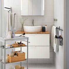On sait ce que c'est, dans une salle de bains, il y a toujours un tas d'objets qui dépassent ou n'entrent pas dans les placards, dont on a besoin tous les jours et qu'on aime avoir à disposition, sans pour autant qu'ils soient négligemment posés sur le rebord de l'évier. Dans cette salle de bains, on aime l'association du meuble lavabo avec sa vasque à poser, très élégant, avec ses rangement bien fermés, du miroir avec rangements, le tout très épuré, avec le chariot mobile, très pratique…
