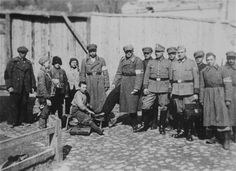 At the main gate to the Krzemieniec (now Kremenets, Ukraine) ghetto, Jewish children polish the boots of Jewish policemen as German soldiers look on.