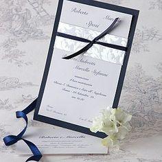 Elegante partecipazione composta da un cartoncino blu, ed uno bianco, legati insieme da un nastro di raso blu e da una fascia argento