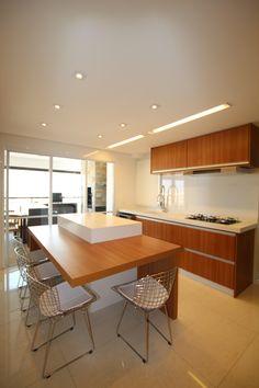Esta cozinha com uma ilha central, é muito prática. Pois além de servir de apoio de pratos, serve como local de refeições rápidas. Projeto e fotografia da arquiteta Pricila Dalzochio
