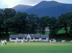 Keswick cricket ground.  Game of cricket in progress at Fitz Park, Skiddaw mountain in background. Voted most beautiful cricket ground in England