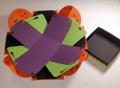 "Wouldn't your Halloween photos look awesome in this brightly colored Halloween Explosion Box with bright, orange, lime green and black layers? Rounded corners on the base layer feature black and purple flying bats, while the three inner layers boast trimmed corners and edges with bats, spiderwebs and broomsticks.  Box is approximately 4"" cube.  Single-sided/flap layer panels are approximately 3 7/8"" x 4"",  3 5/8"" x 4"", and 3 3/8"" x 4""."