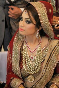 Traditional Indian bride wearing bridal saree, kundan jewellery and hairstyle. Indian wedding photography.