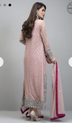 Embrace a timeless style with our net rose gold front open shirt. Blooming with silver kora dabka, pearls and Swarovski crystals, this outfit is artfully coordiNAted with fuchsia pants adorned with beautiful motifs at the bottom. Pakistani Party Wear, Pakistani Bridal Dresses, Pakistani Dress Design, Pakistani Designers, Pakistani Outfits, Indian Dresses, Indian Suits, Indian Wear, Pakistani Clothing