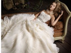 Ivory organza wave bridal ball gown, sheer alencon lace bodice with organza petal accent, platinum jeweled ribbon belt at natural waist, circular skirt, chapel train. Dress available in Ivory.