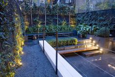 Small Garden, Kensington, stone paving & walls, wood benches, & lots of greenery adds a lot of interest to this smallish city garden