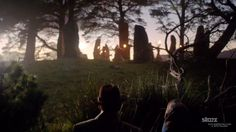 Screencap from first Outlander trailer.  Frank and Claire watch the Druid dancers on Craig Na Dun.