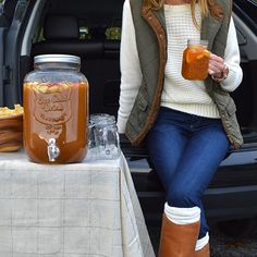 What to wear to a tailgate: Cozy sweater + quilted vest + riding boots