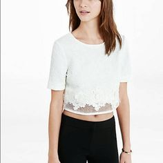 White Floral Lace Crop Top The floral jacquard fabric, lace appliqué at the midriff and mesh hemline on this cropped top add up to a sumptuously feminine and flattering look. This piece exudes a sweet kind of sexiness when you wear it with shorts or a mini skirt.  Crew neck Half sleeves Jaquard fabric with floral lace applique Mesh heml Cropped length Polyester/Spandex body; Polyester hem Hand wash Imported Express Tops Crop Tops
