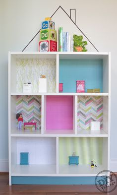 DIY an IKEA bookshelf into a dollhouse, lining each section with different paper to make individual rooms.