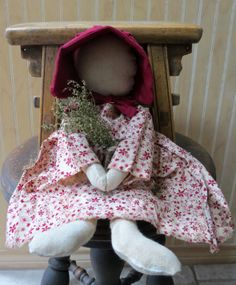 Precious Amish Style Primitive Doll.  She is hand crafted from a pattern found at My Primitive Saltbox.  Her dress is red floral calico and she wears a burgundy bonnet.  In her hands is a bouquet of Sweet Annie.