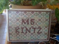 Sign made of unfinished wood, Modge Podge, and scrapbook paper.