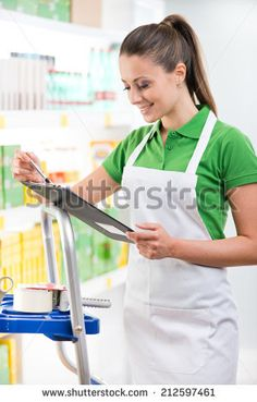 Attractive female sales clerk at work holding a clipboard with supermarket shelf on background.