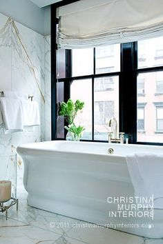 white marble. standing tub. black windows in master bathroom.