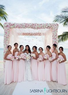 Bridesmaids gather around the bride wearing matching light pink gowns.
