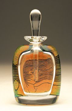"""""""Windy""""  Art Glass Perfume Bottle    Created by David New-Small  Blown glass perfume bottle. Drawings are engraved by hand on gold dichroic glass and melted into the clear glass body. An excerpt from a classic love poem or sonnet appears on the back. Part of the artist's """"Love Songs"""" series."""