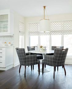 White and gray dining room features a Westport Pendant illuminating a round marble Saarinen Dining Table lined with gray tartan dining arm chairs placed in front of windows dressed in white and gray interlocking circles roman shades.