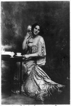 Mrs. Patrick Campbell, actress, full-length portrait, seated at small table, facing slightly right, holding pet dog, ca. 1901.