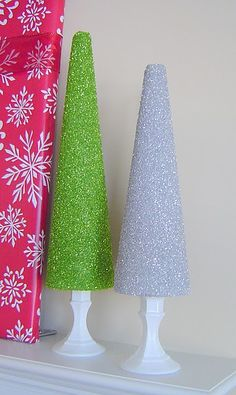 easy DIY - buy styrofoam from a crafts store shaped like a christmas tree. cover in glue (paint on if needed) then dip or roll in sparkles. repeat (once dry) if not enough sparkles stuck.