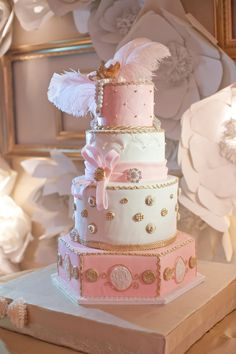 Pink and gold wedding cake with a feather for some sass
