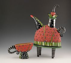 """Red teapot with green pants: Hand-built ceramic teapot, measures 12 1/2"""" tall, 10 1/2"""" wide spout-handle, and 4 3/4"""" deep. This teapot is functional and is made from white earthenware clay and features the use of some underglaze in addition to the regular glazes."""