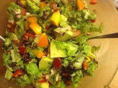 Salade met avocado, kaki, kip, ui en paprika. Dressing van lijnzaadolie, azijn, peper.