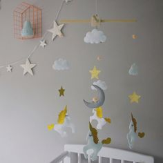 Felt unicorn mobile in golds and white with gold stars with white clouds and peach poms