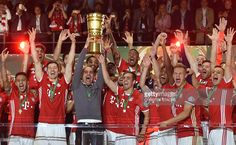 Bayern Munich's players and Bayern Munich's Spanish head coach Pep Guardiola (C) celebrate with the trophy after defeating Dortmund in the penalty shootout of the German Cup (DFB Pokal) final football match Bayern Munich vs Borussia Dortmund at the Olympic stadium in Berlin on May 21, 2016. Bayern Munich won the German Cup.